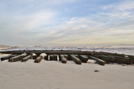stranded: Close up of wooden jetty stranded on the beach Stock Photo