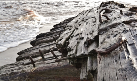 Close up of wooden jetty stranded on the beach Stock Photo