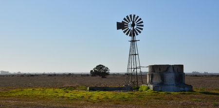 Landscape with windmill waterpump on farm land photo