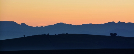 morning blue hour: Landscape with mountains and hills in early morning light Stock Photo