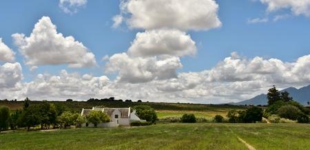 Landschap met boerderij en wolken in de lucht Stockfoto