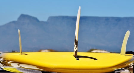 surfen: Close up of a yellow surfboard with Table Montain in the background Stock Photo