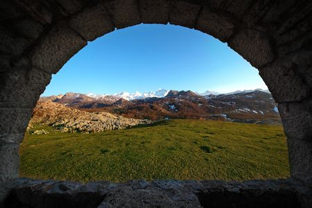 oxigen: Scenic of snowing mountains from a window in a chapel