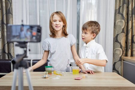 Cute little bloggers with homemade slime recording vlog video on kitchen.