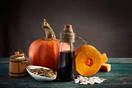 Piece of pumpkin, pumpkin seeds in sackcloth bag and a wooden barrel, hemp seed and oil bottle. Close up.