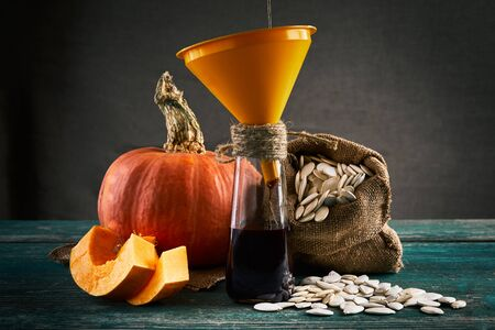 Raw pumpkin, pumpkin seeds on sackcloth bag and oil bottle with yellow funnel. oil pouring process. Close up.