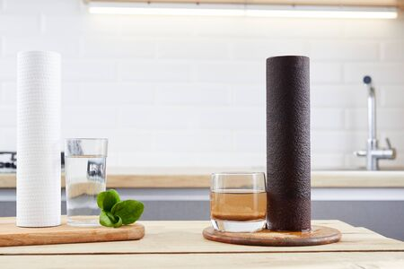 Water filter cartridge used and a glass of dirty water and new pure filter with a glass of clean water from domestic osmosis systems at kithen background. Concept of a water treatment. Stock fotó