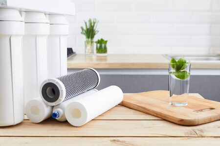A glass of clean water with osmosis filter and cartridges on wooden table in kitchen interior. Concept Household filtration system.