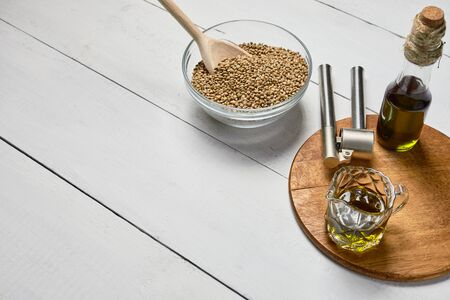 Hemp seed in a glass bowl and garlic pressing masher on the table, Cold pressed oil in a glass jar.