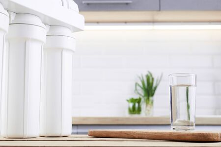 A glass of clean water with osmosis filter on wooden table in a kitchen interior Stock fotó