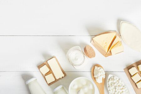top view of dairy and dairy products on a white background. Milk, sour cream, mozzarella, kefir, yogurt, butter, cheese assortment. Flat layout