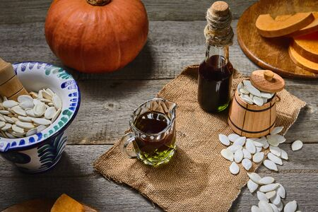 Cold pressed Pumpkin seed oil in a glass bottle and gravy boat, raw pampkin decorated with seeds in pounder and little wooden barrel