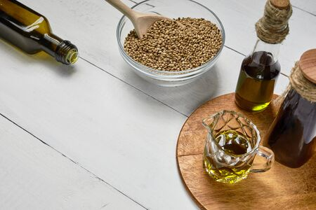 Hemp seed in glass bowl on the table, Cold pressed oil in a glass jar and bottle on the background of wooden boards