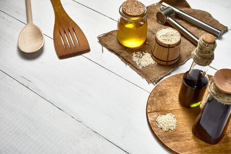 sesame seed in wooden bowl on the table and garlic pressing masher, Cold pressed oil in glass jar and bottle on the background of wooden boards Stock fotó