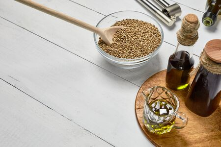 Hemp seed and garlic pressing masher on the table, Cold pressed oil and bottle on the background of wooden boards