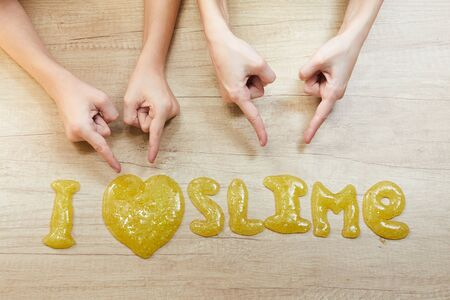 Text I love smile on table. Childs plays with slime. Homemade popular toy slime. Imagens
