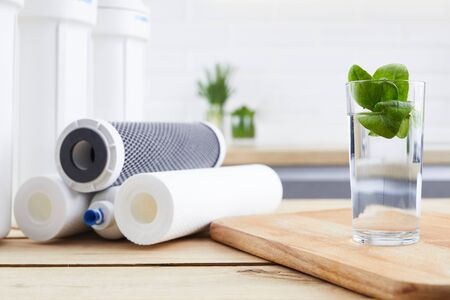 A glass of clean water with osmosis filter and cartridges on wooden table in kitchen interior. Concept Household filtration system. Banco de Imagens