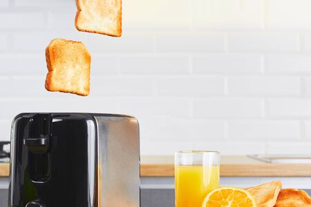Toaster with dishes and toast with fresh juice on a kitchen table