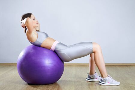 Young fit woman exercising in a gym. Sports girl is training cross fitness with a Pilates Balls.