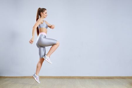 Fit young woman doing cardio interval training in gym. Woman in sportswear posing and jumping. Fitness concept.