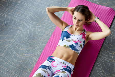 Sporty young woman wearing fashion sports wear and lying on yoga mat doing abs crunches. Top view Reklamní fotografie