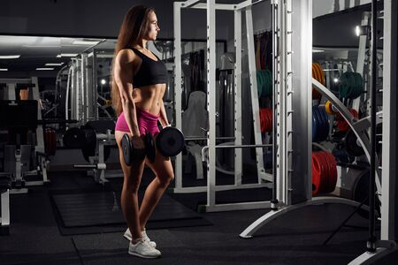 Brutal athletic girl pumping up muscules with dumbbells and showing her trained body . Foto de archivo