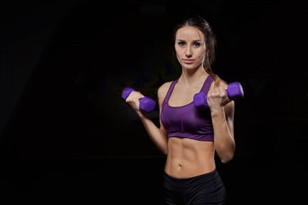 Beautiful fitness woman with lifting dumbbells. fit woman works out with dumbbells on dark background. Sporty girl showing her well trained body.