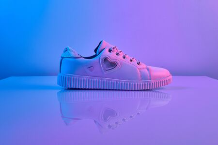 Trendy white teenage sneakers in trendy neon light. Shoe in retro surreal red, blue gradient light. Creative minimalism. Close up Foto de archivo