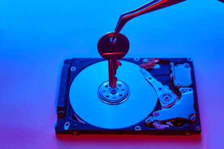 Data security concept. Key on spindle of hard disk drive. Opened Hard disk.