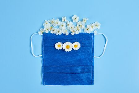Face mask with flowers on blue background. respirator - breathing protection against air pollution or virus. Фото со стока