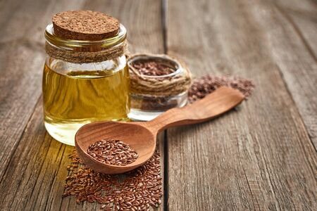 Flax seeds and a wooden spoon with bottle of oil on a wooden table. Healthy food and drink concept. Copy space. Close up