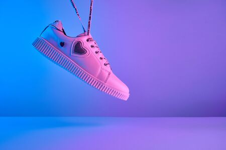 Trendy white teenage sneakers with flying laces in trendy neon light. New shoe in retro surreal red, blue gradient light, Close up