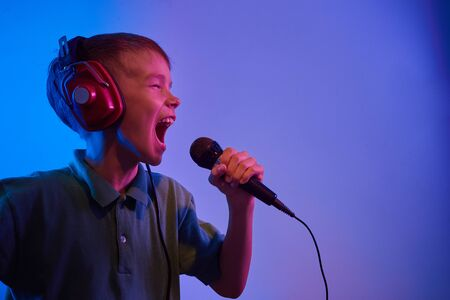 Caucasian teen boy portrait on blue neon light. Male model with microphone singing karaoke.