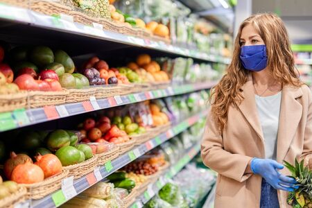 Shopping during the coronavirus Covid-19 pandemic. Woman in facial mask and gloves buys citrus fruit at market.