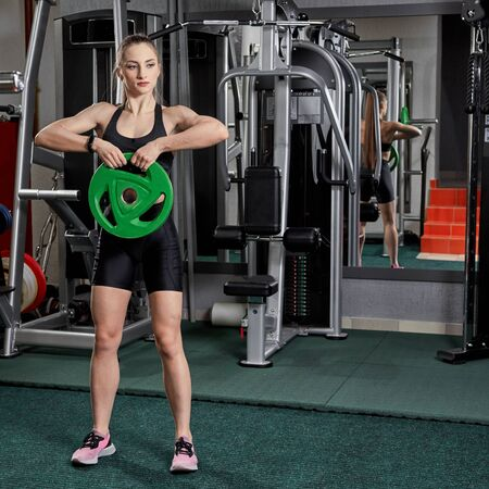Beautiful fitness woman with lifting dumbbells. Fit woman works out with dumbbells on dark background.