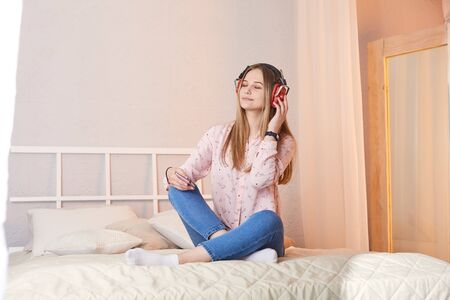 Girl in casual wear listens to music with headphones and sits on bed at home.She using earphones and smartphone for phone video call.