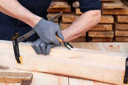 Carpenter's hands that work with cutter. Man working with plane on wooden background. Joiner work in the carpentry.