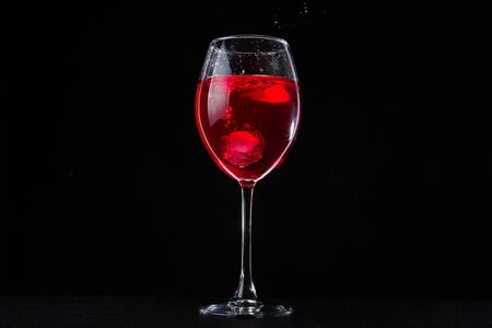 A glass of red vine on black background. Wine glass on dark table. Cabernet drink. Фото со стока
