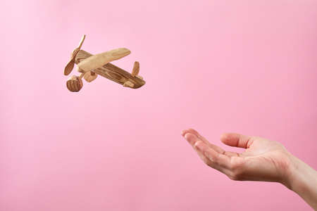 Concept soft landing or airline safety, security and insurance. Female hand and airplane on a pastel pink background