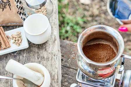 Hot drink on nature. Process of cooking coffee with spices in nature. Background - camping and forest. Active rest. 스톡 콘텐츠