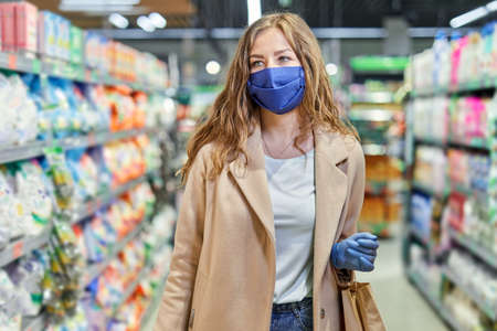 Shopping during the coronavirus Covid-19 pandemic. Woman in facial mask and rubber gloves buys grocery things at the supermarket.