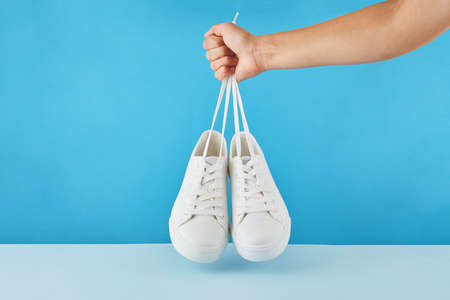 The hand holds by shoelaces Pair of fashion stylish white sneakers on a pastel blue background. 版權商用圖片