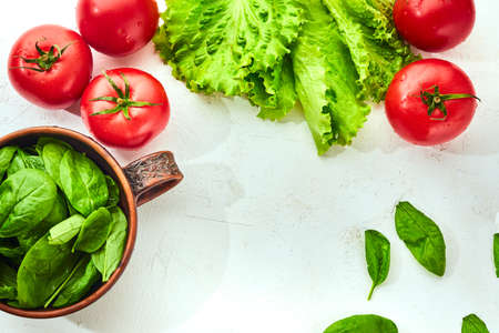 Fresh grape tomatoes with salad and spinach Leaves on white background. Vegan veggies diet food. Herb, tomatoes, cooking concept.