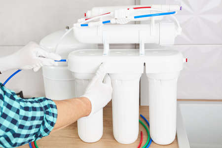 Installation purification osmosis system. Plumber or man hand replace water filter cartridges at home kitchen. Close up.