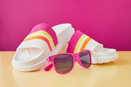 Summer travel concept. Flip flops or slippers and sunglasses on a pastel background. Beach accessories.