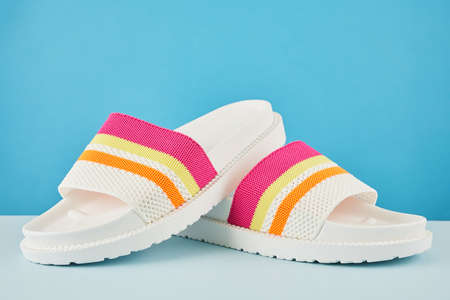 Pair of colorful multicolored rainbow flip flops or sandals on pastel background. Beach holidays and Summer concept with copy space.