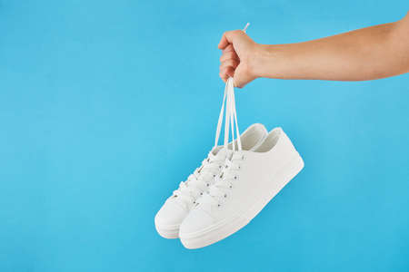 The hand holds by shoelaces Pair of fashion stylish white sneakers on a pastel blue background.