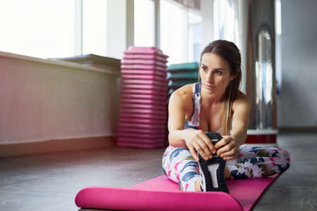 Healthy woman fitness mat doing warmup exercise. Fit woman sitting on a exercise mat stretching.