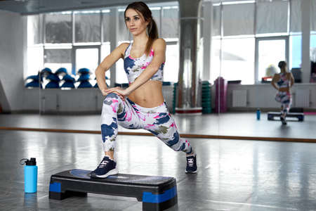 Sporty woman doing lunges with Aerobic Step. Photo of muscular woman in fashionable sportswear on gym. Strength and motivation. Zdjęcie Seryjne