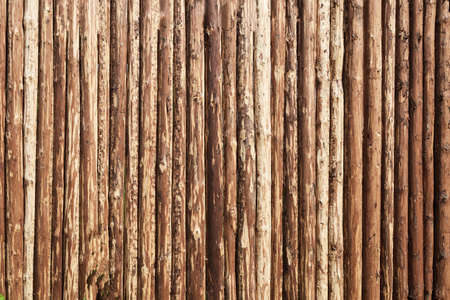 Wooden surface. Aged natural background. Fence made of tree trunks.